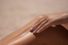Sunscreen at the beach on the leg Royalty Free Stock Photos
