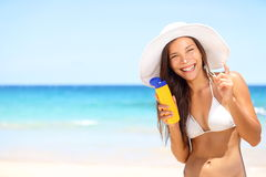 Sunscreen beach woman in bikini applying sun block. Solar cream for UV protection. Girl smiling to camera, wearing white sun hat, happy on vacation travel Stock Images