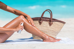 Sunscreen beach woman putting sunblock oil on legs Royalty Free Stock Photo