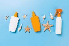Sunscreen bottles with seashells on blue table top view royalty free stock photo