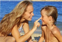 Sunscreen care, sun protection. Mum putting sun cream, sunscreen care or protection on child Royalty Free Stock Images