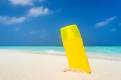 Sunscreen cream bottle on the beach Royalty Free Stock Photography