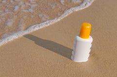 Sunscreen cream bottle on the beach Royalty Free Stock Photos
