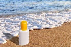 Sunscreen cream bottle on the beach Royalty Free Stock Photo