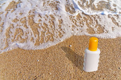 Sunscreen cream bottle on the beach. Close Royalty Free Stock Photos
