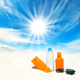 Sunscreen cream and bottle of water over sunny blue sky. Background. Sun protection concept Royalty Free Stock Image