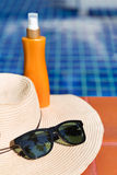 Sunscreen cream and sun glasses with straw hat swimming po Stock Photography