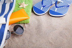 Sunscreen with flip flop. And sunglasses on beach sand royalty free stock image