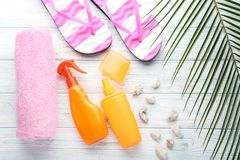 Sunscreen with flip flops and towel. On white wooden table royalty free stock images