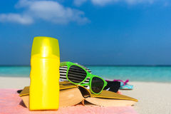 Sunscreen, hat and sunglasses on tropical beach Royalty Free Stock Images
