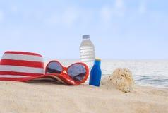 Sunscreen, hatten, solglasögon och flaskan av vatten på sand sätter på land royaltyfri fotografi