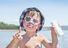 Sunscreen is on hipster boy face before tanning during summer holiday on beach. Caucasian child (kid) have sunglasses, hat and holding container of suntan Stock Photos