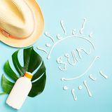Sunscreen large sheet of tropical plant summer hat bright blue background phrase SUN. Summer holiday concept and beach. royalty free stock photo
