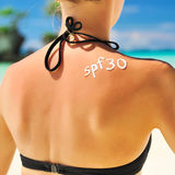 Sunscreen lotion. Over tan woman skin made as SPF 30 word Royalty Free Stock Images