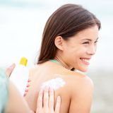 Sunscreen lotion on beach. Couple applying sunscreen lotion. Woman smiling happy on summer vacation. Mixed race Caucasian / Asian Chinese young woman royalty free stock photography