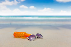Sunscreen lotion and dark glasses on the beach for summer time Royalty Free Stock Image