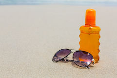 Sunscreen lotion and dark glasses on the beach for summer time Royalty Free Stock Photos