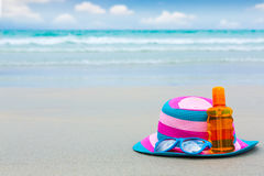 Sunscreen lotion and dark glasses with hat on the beach for summ Stock Image