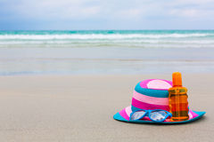 Sunscreen lotion and dark glasses with hat on the beach for summ Royalty Free Stock Photo
