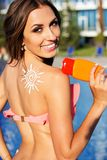 Sunscreen lotion on girls shoulder near swimming pool Stock Photos