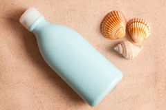 Sunscreen in sand Stock Photography