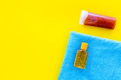 Sunscreen for sea vacation. Bottles with cream or lotion near towel on yellow background top view copy space royalty free stock photography