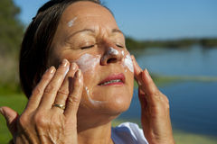 Sunscreen Skin Cancer Protection. Portrait of a Mature Woman putting lotion of sunscreen on her face to protect her skin against the UV rays