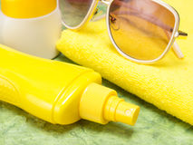 Sunscreen spray bottle, jar of sun cream, towel and sunglasses. Sun protection cosmetic products. Close-up, very shallow depth of field Stock Images