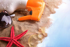 Sunscreen spray and sunglasses on sand in table Stock Photography