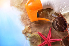 Sunscreen spray and sunglasses on sand in table top view Stock Photos