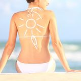 Sunscreen / sun tan lotion. Sun drawing on woman back. Girl in bikini sitting on beach in sunlight Royalty Free Stock Images