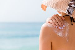 Sunscreen sunblock. Woman in a hat putting solar cream on shoulder outdoors under sunshine on beautiful summer day.  royalty free stock photography
