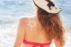 Sunscreen tan lotion sun drawing on woman back Royalty Free Stock Photos