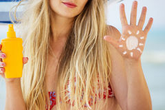 Sunscreen and tanning. Girl smeared sunscreen at the beach Stock Photo