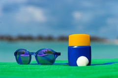 Sunscreen, towel and sunglasses on tropical beach Stock Photography