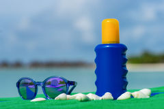Sunscreen, towel and sunglasses on tropical beach Stock Images
