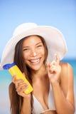 Sunscreen woman applying suntan lotion laughing. Beautiful vivacious laughing woman in a sunhat and bikini applying suntan cream from a plastic container to Stock Photo