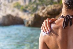 Sunscreen on a woman`s shoulder. Woman rubs sunscreen on his shoulder. Against the background of the sea stock photography