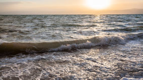 Sunsdown e spuma in mare il mar Morto nel crepuscolo di inverno Immagine Stock