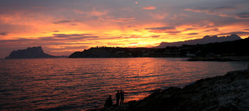 Sunset. At the seaside in Moraira, Spain, viewing the Peñón d'Ifac and the Bernia mountain range Stock Photo