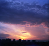 Sunset. Over a city with beautifully lit clouds Royalty Free Stock Images