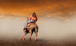 Into the Sunset. A lady riding off into the sunset on a horse Royalty Free Stock Images