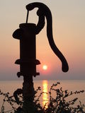 Sunset. An old water-pump is in the front of the sun Stock Images