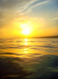 Sunset. Photo of yellow sunset, blue sky and dark sea royalty free stock photo