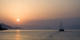 On a sunset. Mountains and ship on a sunset bay Royalty Free Stock Photography