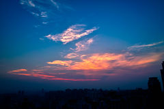 Sunset. Over a city, accentuated by dust particles. Very clear and bright perspective with clouds layers that accentuate the horizon, while several sun rays Royalty Free Stock Photo