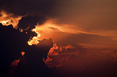 Sunset. Dramatic red sunset sky with sun behind a cloud stock image