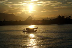 Sunset. At sarawak river with a silhouette man paddling boat Royalty Free Stock Image