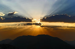 Sunset. Sun rays at sunset in the clouds on the mountains Stock Photography