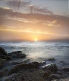 Sunset. Over the sea, stony seacoast Stock Photo